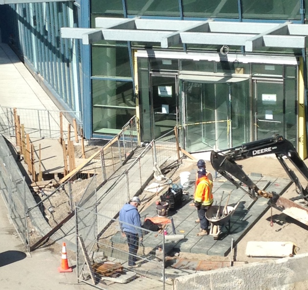 Laying the new pavers for the sidewalk on the north side of the The Esplanade at the main entrance to the L Tower.