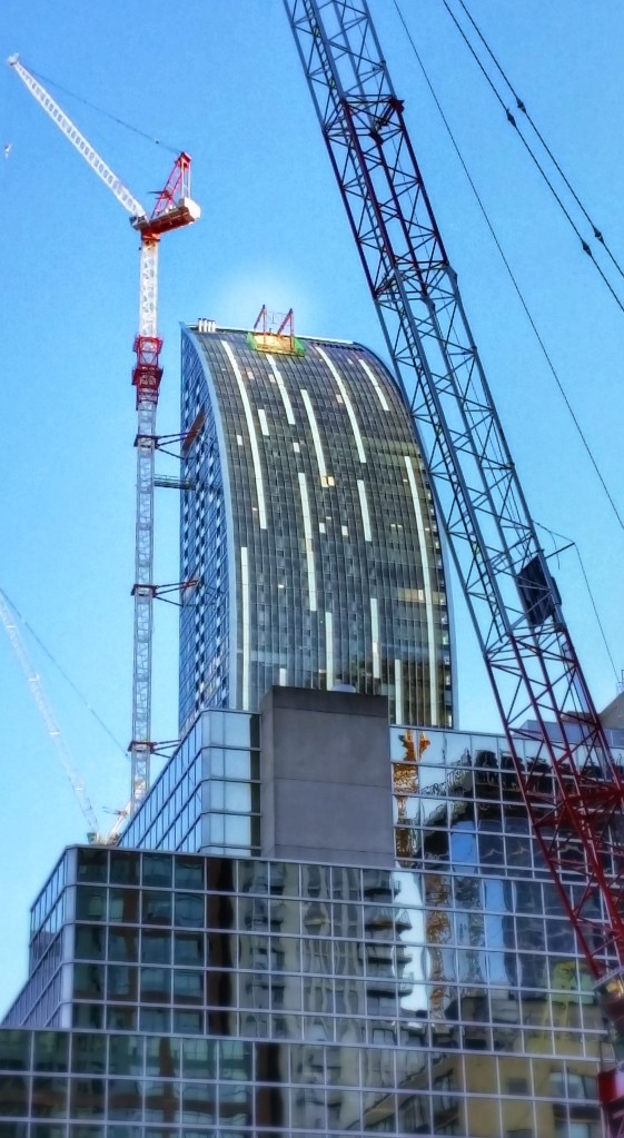 L Tower with temporary window washing crane platform and tower crane