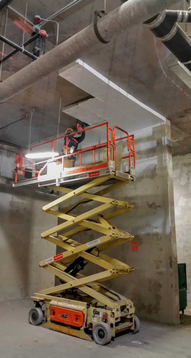 Installing insualtion in the first floor parking garage at Backstage
