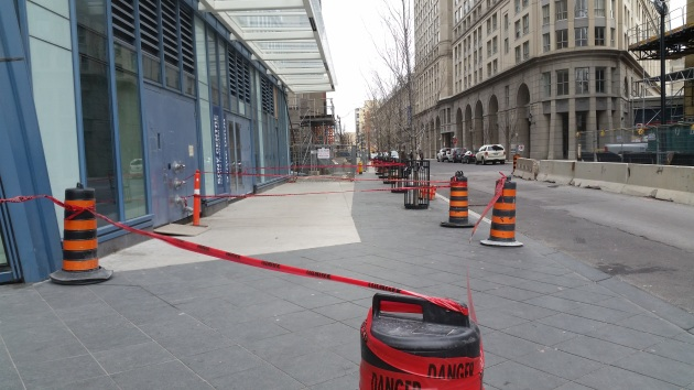 Sidewalk taped off for safety reasons in preparation for the begining of the tower crane removal